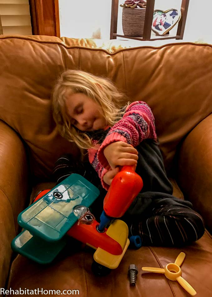 Daughter taking apart toy airplane, this toy comes with electric screwdriver and is built to be disassembled. Young girl pre-schooler concentraing while sitting on leather chair in overalls and sweater working on removing a screw or bolt holding the tail onto the plane.