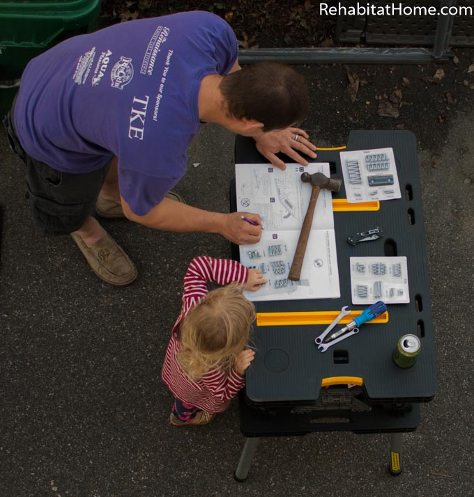 Dad and daughter examine instructions for putting together an outside storage container. Dad reads each step and little girl follows along. Instructions are sitting outside on a work bench, a hammer is used to keep the pages from blowing in the wind.